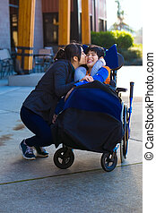Older sister kissing little disabled brother in wheelchair outdoors