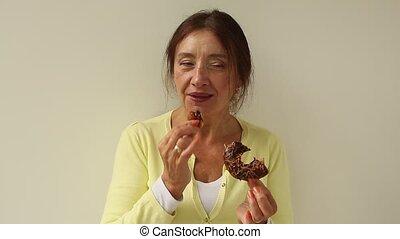 Older woman bites into a fresh bakery doughnut