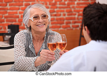 Older woman drinking rose wine in a restaurant with a young man
