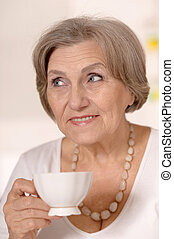Portrait of a happy older woman at home drinking tea