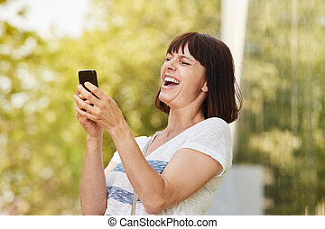 Older woman laughing looking at smart phone