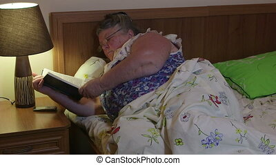 Older woman lying in bed reading book before dozing off at night