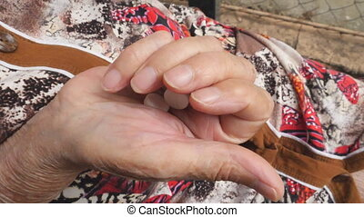 Older woman putting two white pills in her arm. Grandmother...