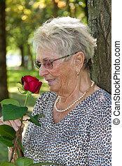 Older woman (senior citizen) smelling a red rose
