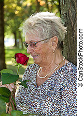 Older woman (senior citizen) smelling a red rose