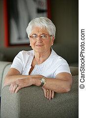 Older woman sitting on a sofa