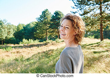 Older woman smiling standing in nature