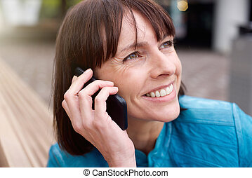 Older woman smiling with mobile phone outside