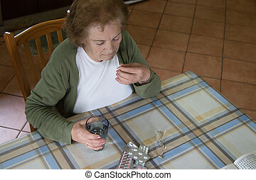 older woman taking medication at home
