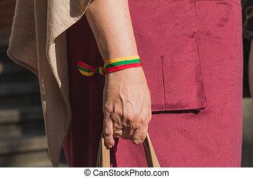 Older woman wears lithuanian flag band on a wrist
