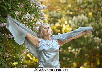 Older woman with flowers - Portrait of a happy beautiful...