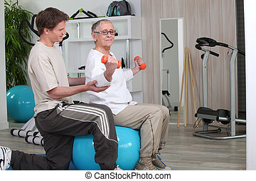 Older woman working out with a personal trainer at the gym