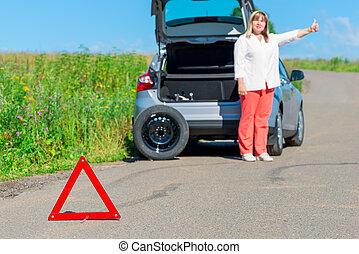upset woman on the road near the broken car