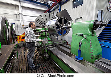 Older workers in the metal industry in CNC milling machine.