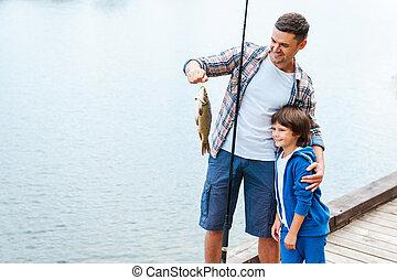 olhar, que, nós, caught!, pai, segurando, cana de pesca, e, mostrando, peixe grande, para, seu, filho