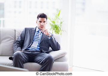 olhar, sofá, câmera, homem negócios, sério, sentando