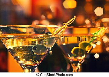 Olive and glass Martini with candle - shallow dof