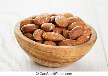 olive bowl full of almonds on wood table