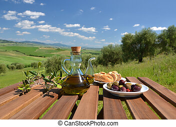 Olive oil and olives on the wooden table against Tuscan ...