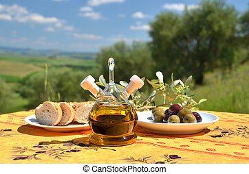 Olive oil and olives on the wooden table against Tuscan...