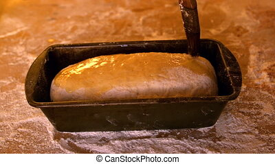 Olive oil being brushed over dough in loaf tin on a floury...