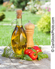 Olive oil bottle, pepper shaker, tomatoes and herbs on ...