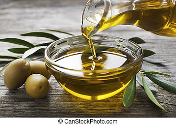 Bottle pouring virgin olive oil in a bowl close up