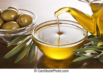 Olive oil - Bottle pouring virgin olive oil in a bowl close...