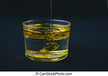 Olive oil falling on water in a low glass with drops of oil on the bottom