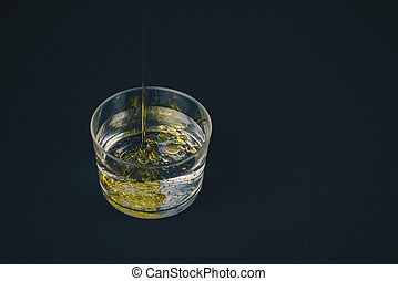 Olive oil falling on water in a low glass with drops of oil on the bottom.