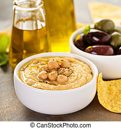 Olive oil homemade hummus with olives and corn chips