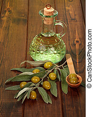 Olive oil in bottle and olives on table