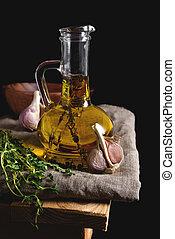Olive oil in glass bottleon linen napkin on a dark background