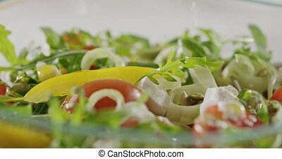 Olive oil is poured a glass bowl with a salad of organic...