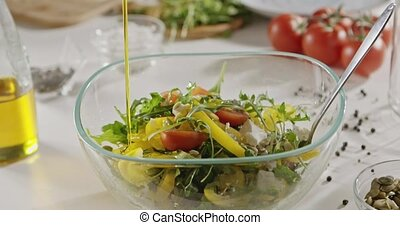 Olive oil is poured a glass bowl with spoon with a salad of...
