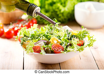 olive oil pouring into bowl of fresh salad