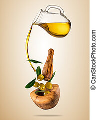 Olive oil with flying olives in wooden bowl