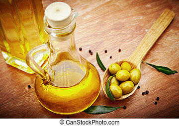 Olive oil with fresh olives on rustic wood - Extra virgin...
