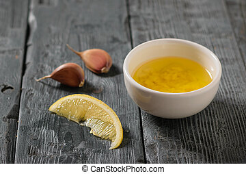 Olive oil with garlic and lemon in a white bowl on a dark table. Dressing for diet salad.