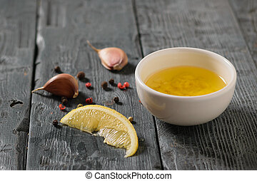 Olive oil with garlic and lemon in a white bowl on a village table. Dressing for diet salad.