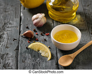 Olive oil with garlic and lemon in a white bowl on a wooden table. Dressing for diet salad.