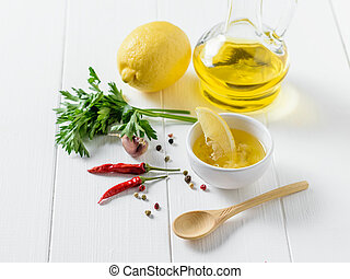 Olive oil with garlic, pepper, parsley and lemon in a white bowl on a table. Dressing for diet salad.