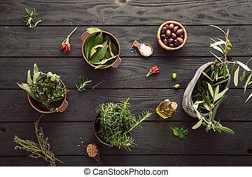 Olive oil with herbs. Mediterranean ingredients: rosemary, olives, thyme, sage, salt, oregano