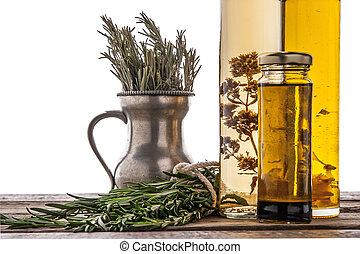 Olive oil with herbs on the wooden table