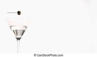 Olive on a skewer falling in super slow motion in a Vodka...