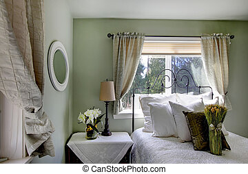 Olive tones bedroom with antique iron frame bed and beige curtains