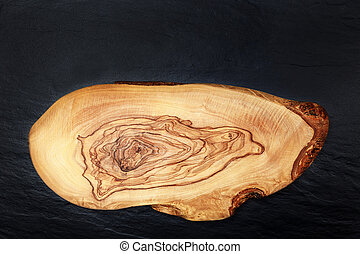 Olive wooden cutting board on the black background