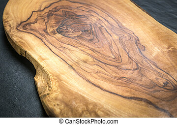 Olive wooden cutting board on the black stone background