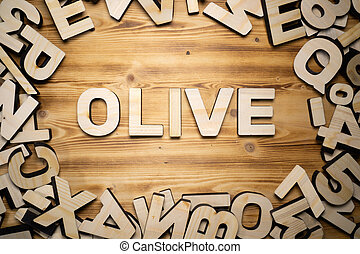OLIVE word made with block letters lying on wooden board