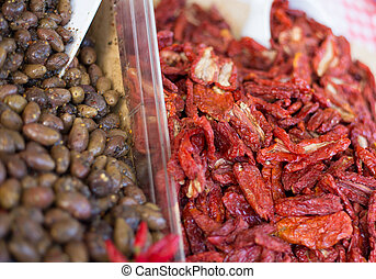 olives and dried tomatoes on sale in the market of Italy